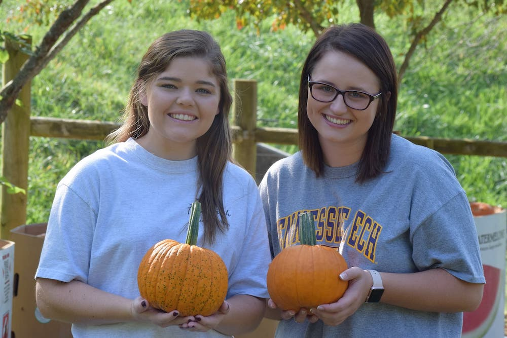 Students pass out pumpkins at the annual fall festival