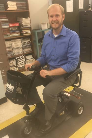 Dr. Charles Van Neste on a wirelessly charged scooter