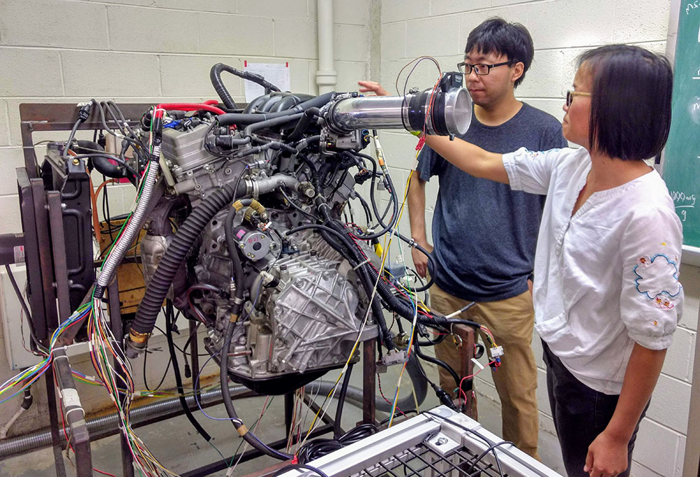 Two students working in the Automotive Powertrain and Emissions Control Lab
