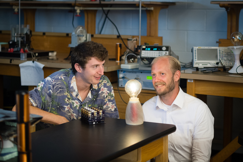 Electrical engineering master's student Tanner Mingen, left, looks at the wireless charging module with Charles Van Neste, research assistant professor with CESR.