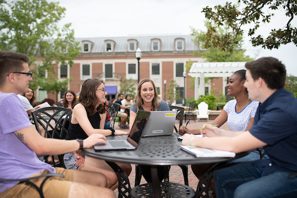 Photo of five students sitting at a table on Centennial Plaza