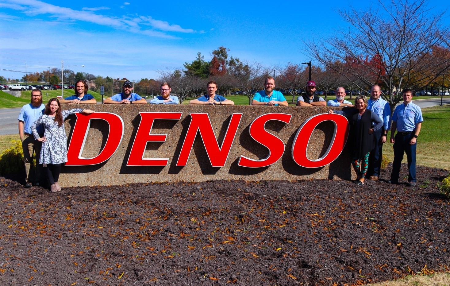 DENSO sign surrounded by employees who are Tech graduates