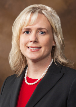Portrait of Jennifer Taylor - she has shoulder-length blonde hair and is wearing pearls, a red blouse, and black blazer