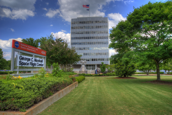 The outside of the George C. Marshall Space Flight Center - there is a mowed green lawn and a tall building with the American flag on top.