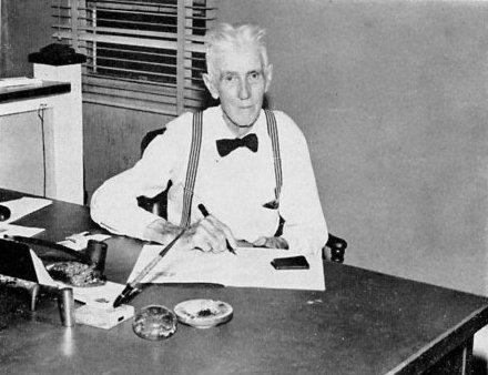 A black and white photo of Alvin G. Maxwell sitting at a desk holding the pen.