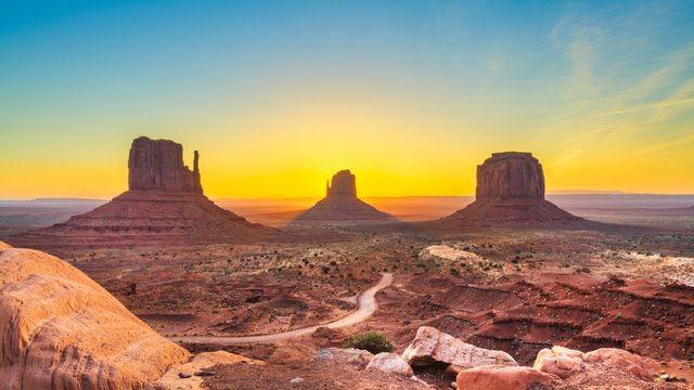 A sunrise over the Utah desert. There are four buttes in the distance and layered rock in the foreground.