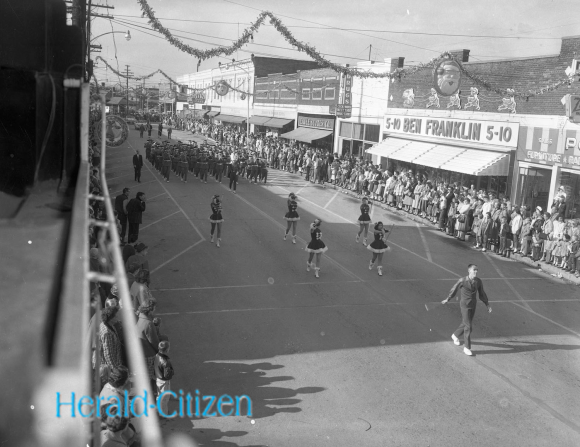 1960 Photo of Cookeville Christmas parade with baton twirlers and a band marching down Broad Street in front of the 5-10.