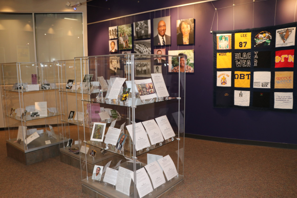 Photo of glass display cases with photographs and text and a canvas photo display on the purple wall behind it.