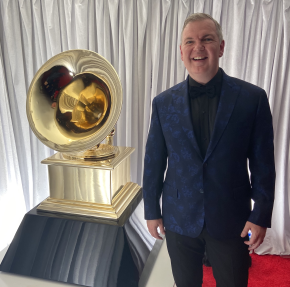 Craig Terry, wearing a dark blue damask suit jacket and smiling, stands beside a large replica of a grammy award