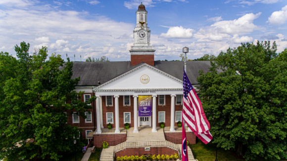 Aerial view of Derryberry Hall with a bright blue sky and white clouds. The American flag is in the foreground of the photo.