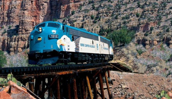A blue Verde Canyon Railroad train with the number 1512 goes across a bridge with an outcrop of red and brown sandstone behind it.