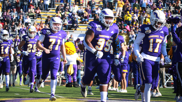 Football players run onto the field in Tucker Stadium. The stands behind them are full of onlookers wearing gold and purple.
