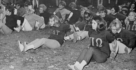 Sorority particpating in game where they are sitting on the ground and holding onto the feel of the person behind them.