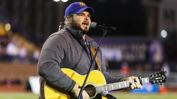 Jake Hoot singining playing the guitar and singing the national anthem at a TTU football game.
