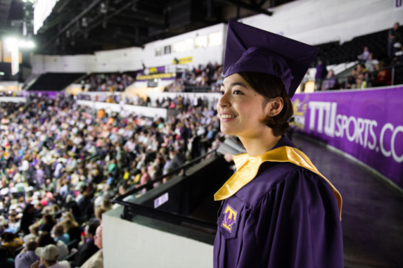 A female student in her purple cap and gown stands at the top of Hooper Eblen smiling at the crowd gathered for commencement.