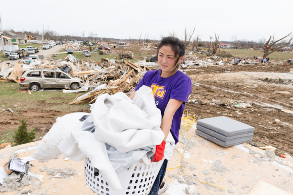 A female student carries a laundry basket of bedding. Threre are piles of wood and debris behind her  - what remains of homes destroyed by the tornadoes.