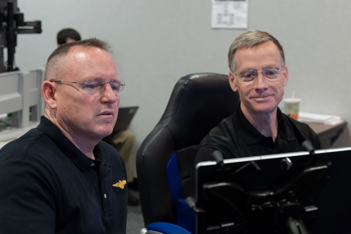 Photo of Barry Wimore looking at a computer monitor next to another gentleman.