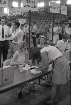 photo circa 1969 - female student registering for a foreign language at a table set up on the floor of memorial gym