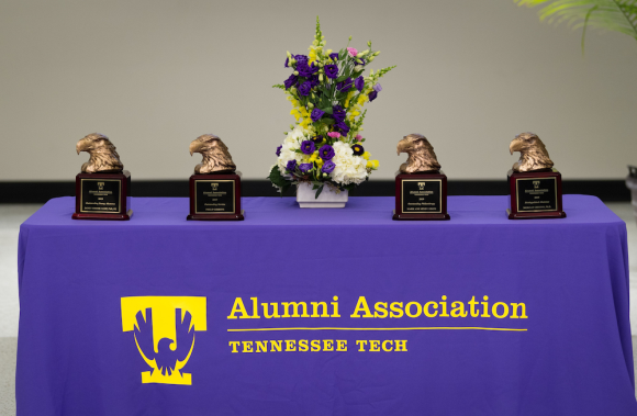 "Bronze eagle head alumni awards sit on a table with a cloth reading ""Alumni Association, Tennessee Tech"""