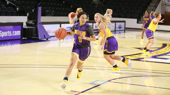 Tech women's basketball still of woman dribbling ball in a scrimmage.